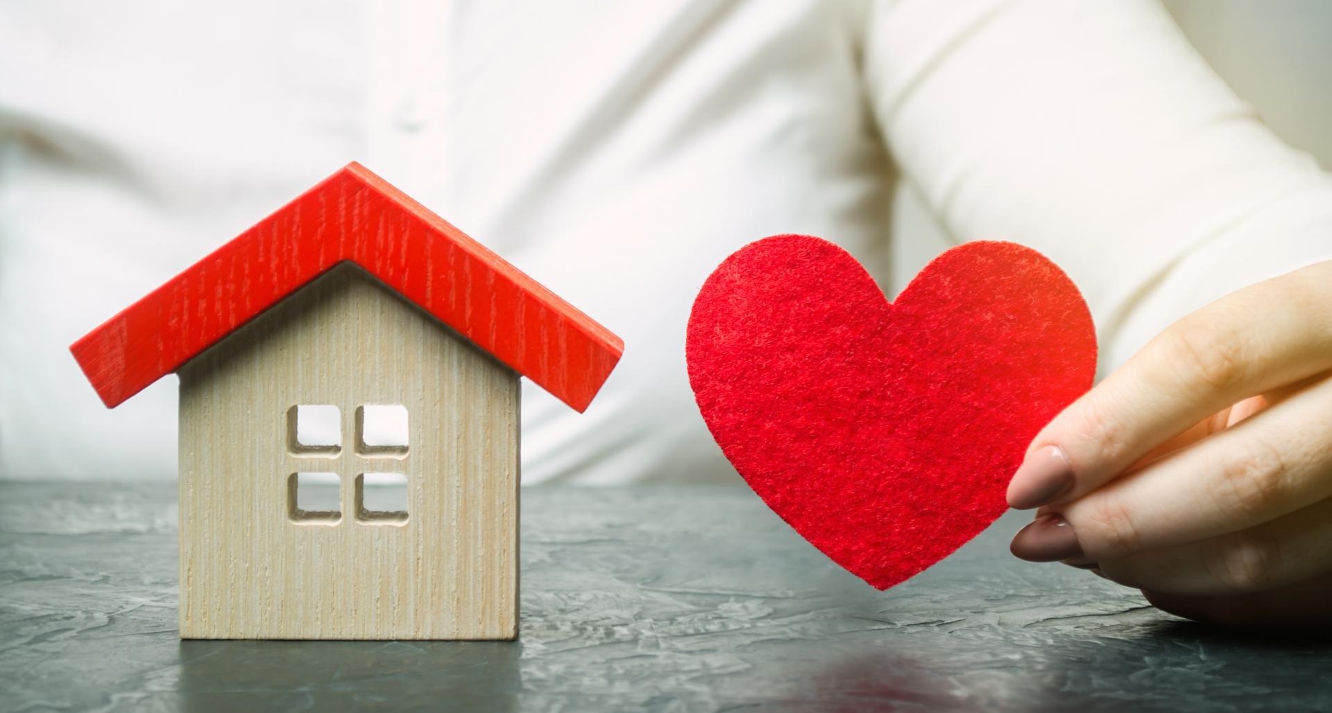 Une femme tient un coeur en feutre à côté d'une petite maison en bois