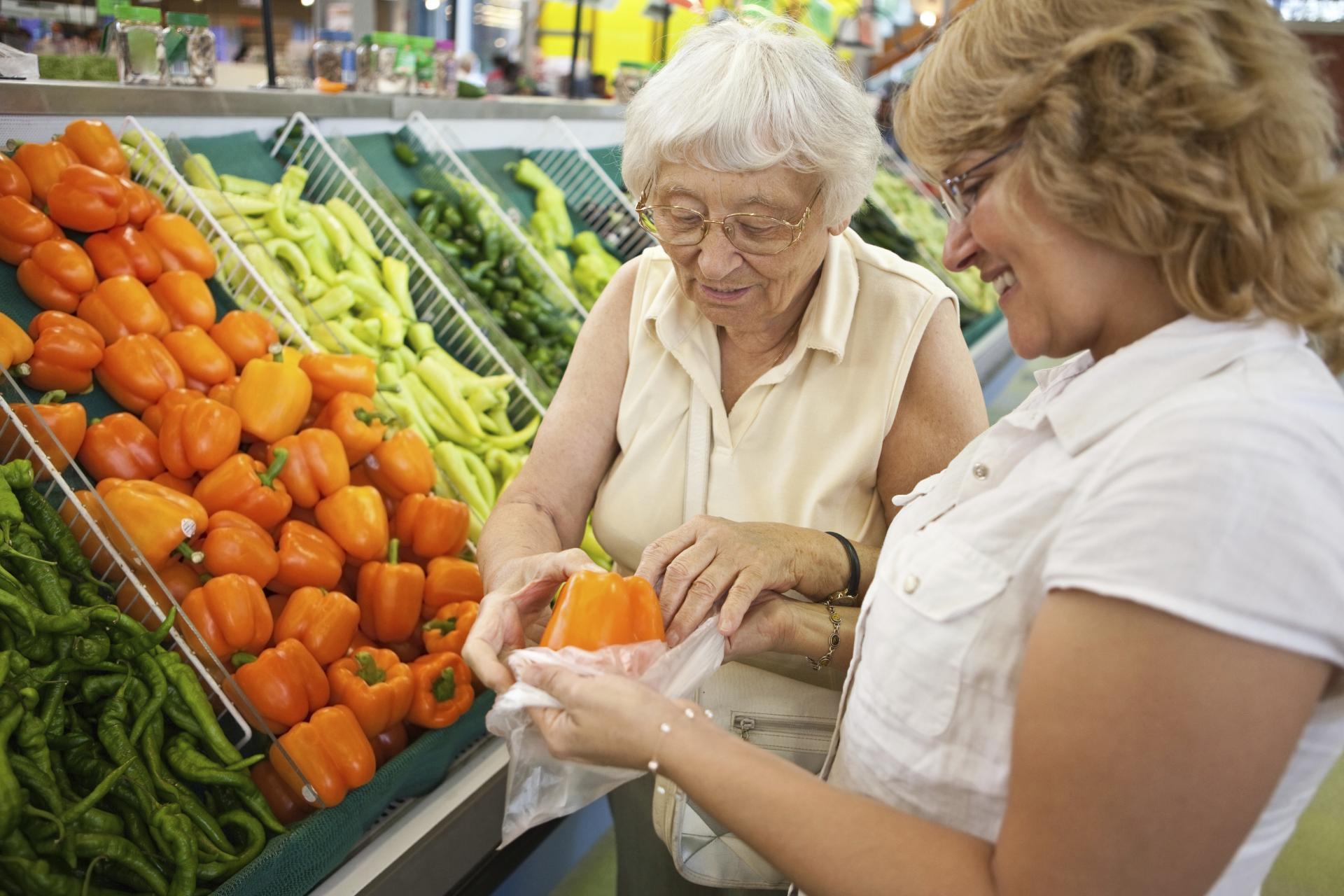 Une femme aide une personne âgée à faire les courses.