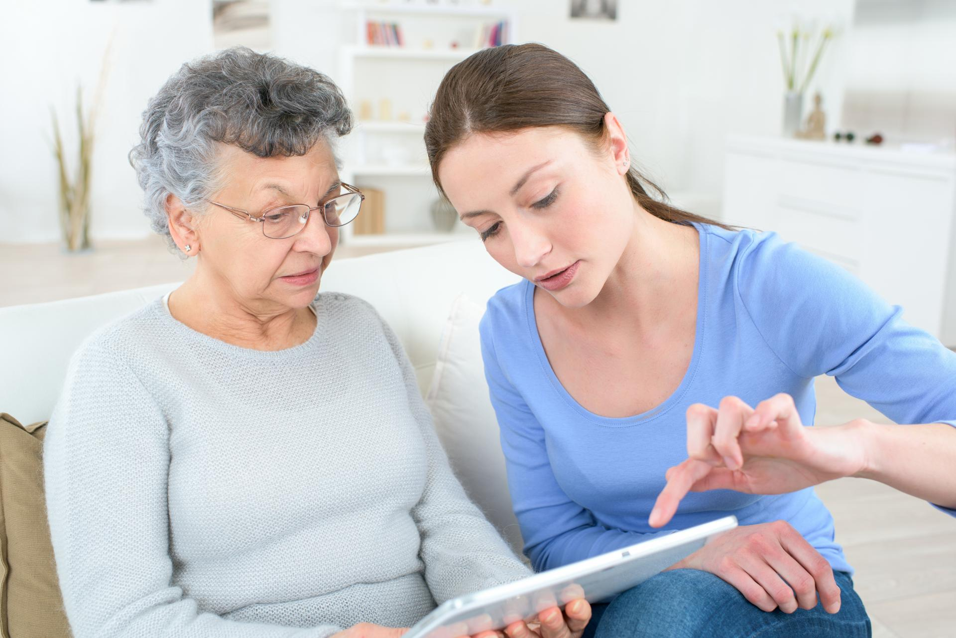 Une jeune femme aide une personne âgée à utiliser une tablette numérique.