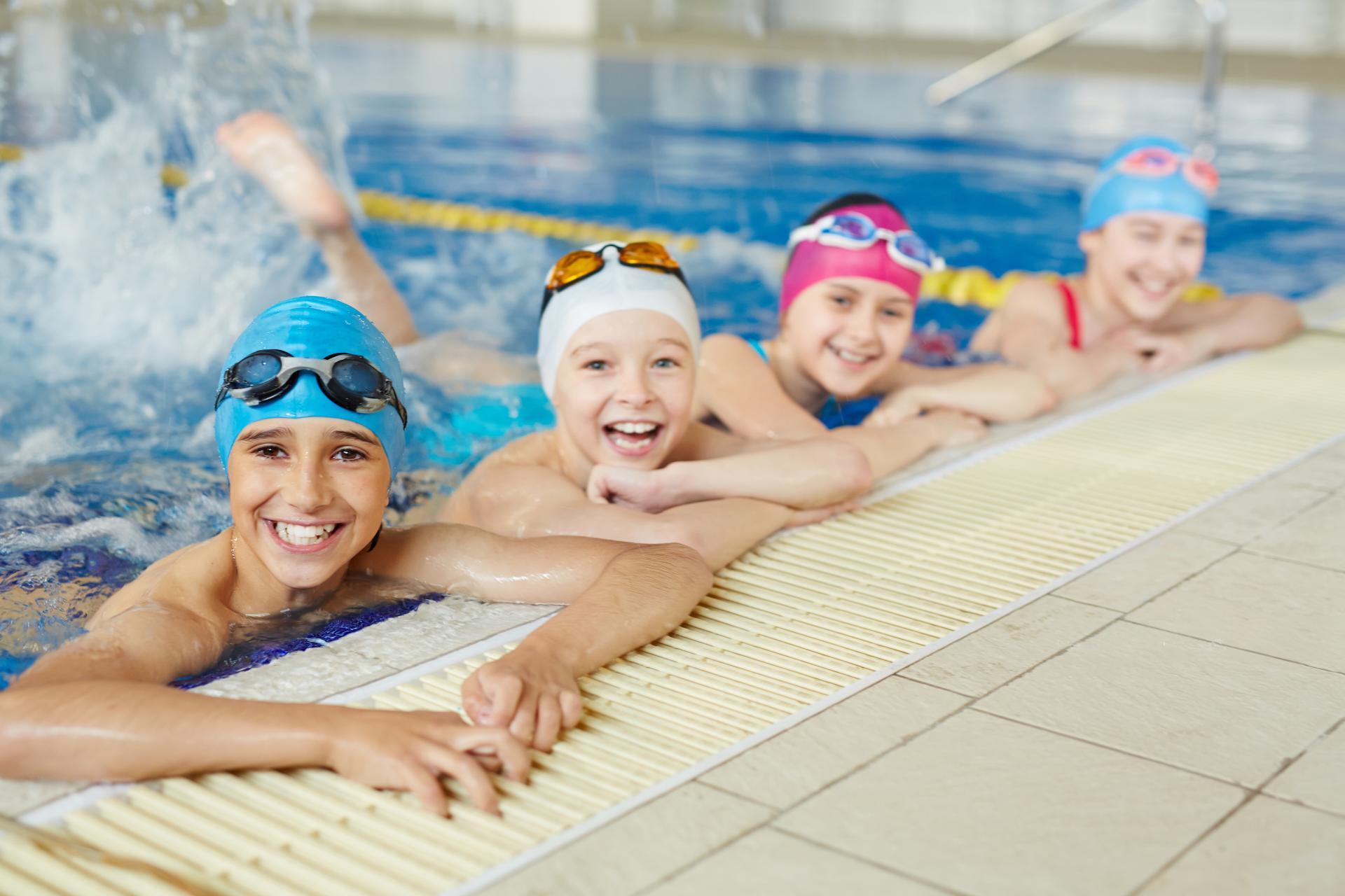 Quatre enfants souriants sont appuyés sur le bord du bassin d'une piscine