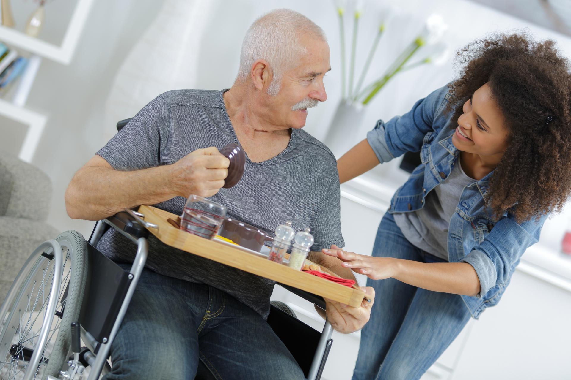 Une jeune femme apporte un repas à un monsieur âgé en fauteuil roulant.