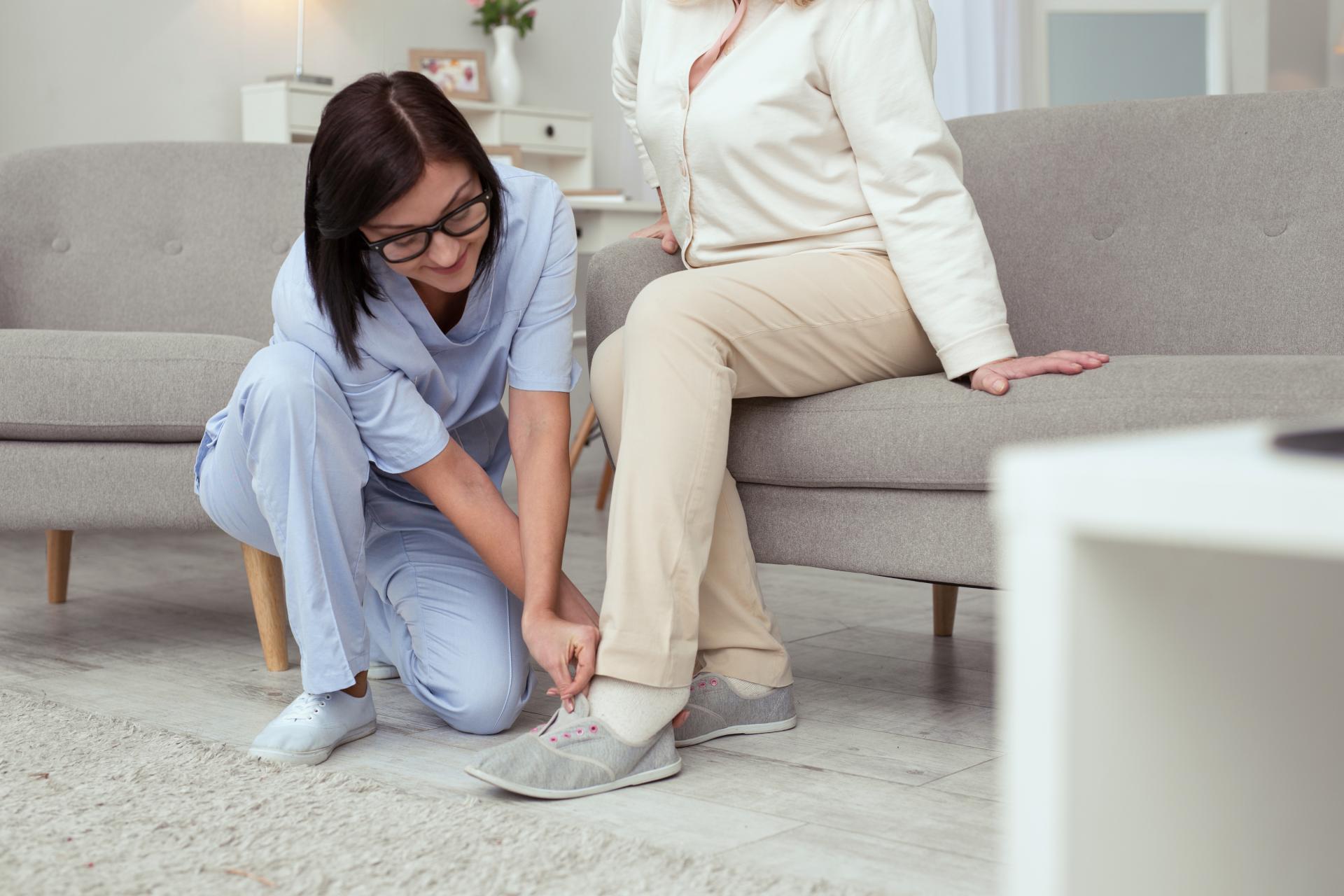 Une aide-soignante aide une personne âgée à mettre ses chaussures.