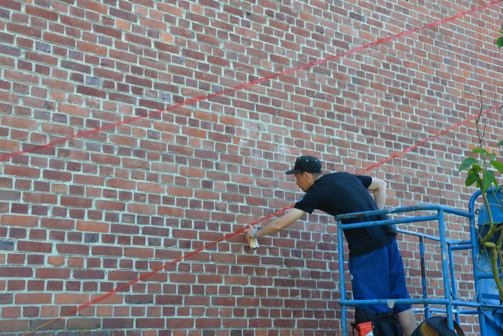 L'artiste ASTRO commence la réalisation de sa fresque.